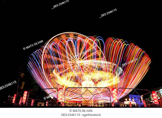 Colourful lights blurring on amusement park rides at night; Locarno, Ticino, Switzerland