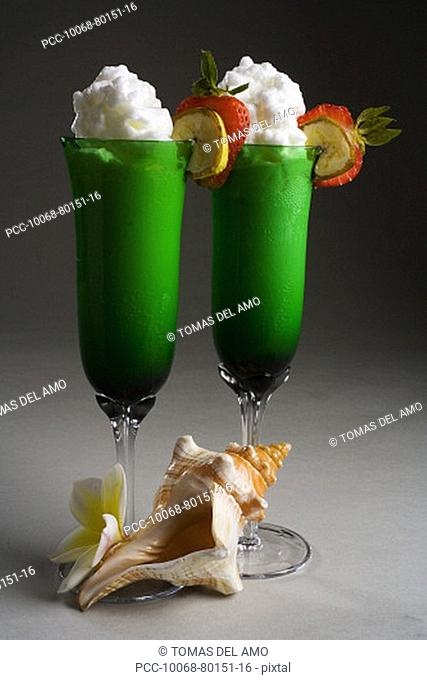 Close-up of two green glasses filled with a creamy tropical drink