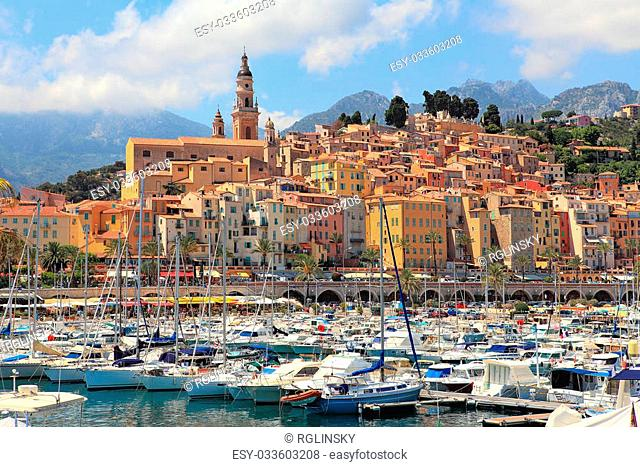 View on colorful houses, church and marina with yachts and boats in Menton - town on French Riviera in France