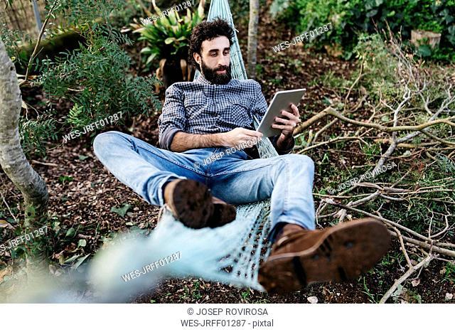 Man lying in hammock using tablet