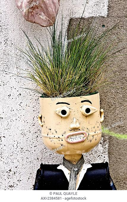 A plant growing out of the head of a unique planter like a male figure; France