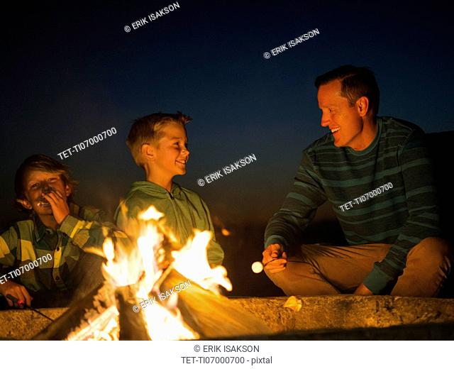 Man talking with his sons (10-11, 14-15) by campfire