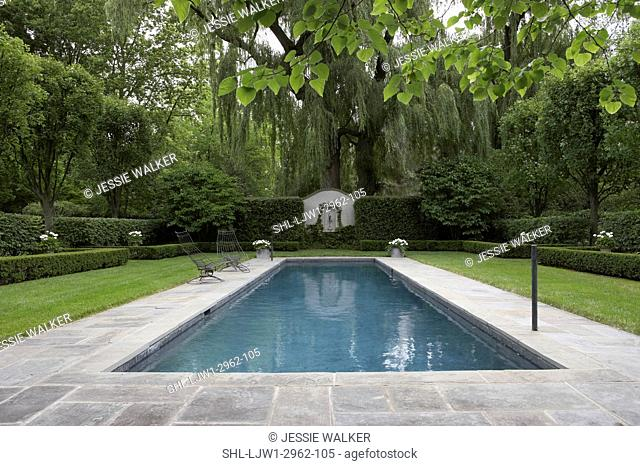 SWIMMING POOLS: Formal shaped hedge garden with narrow pool , bluestone patio, white flowers in grey containers, straight on view with NO curved edge of patio...