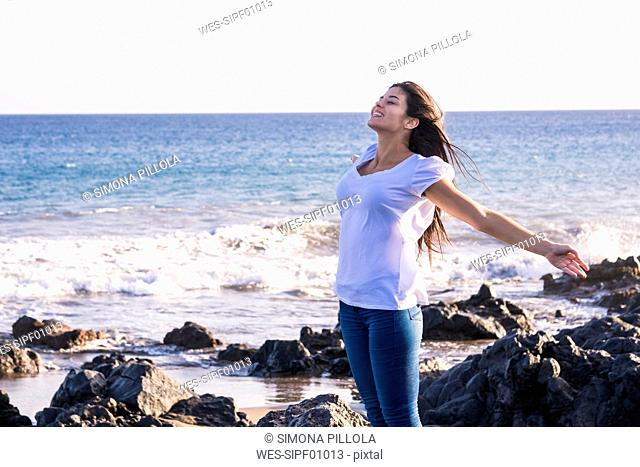Young woman on the beach stretching out her arms