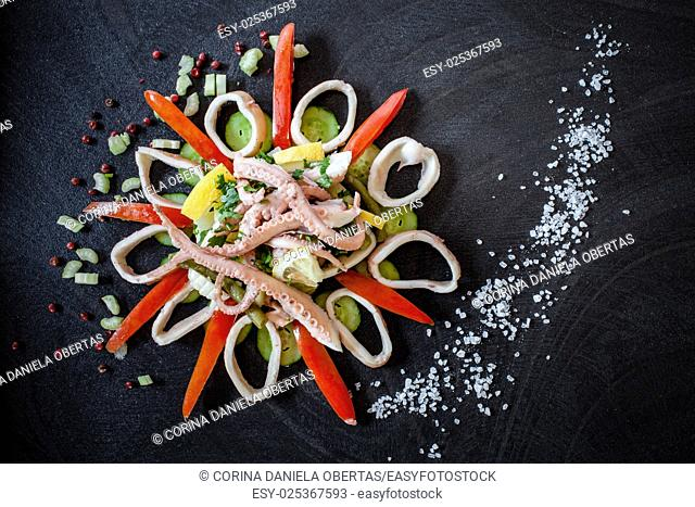 Boiled octopus on fresh vegetables, decorated with coarse salt and red pepper