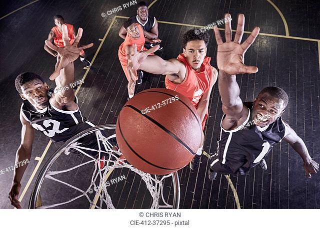 Overhead view young male basketball players jumping to rebound basketball at net on basketball court