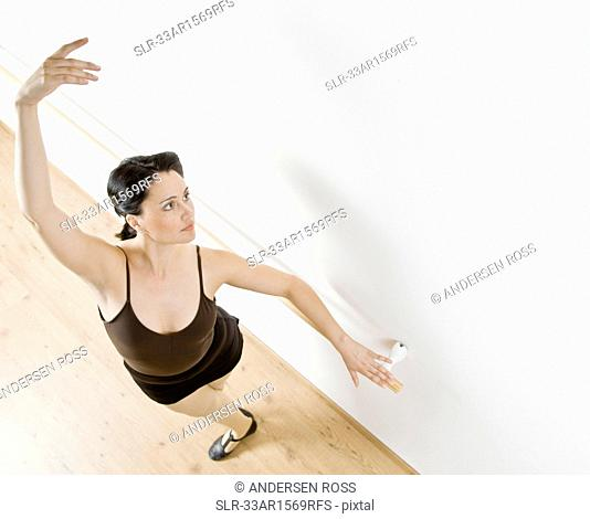 Dancer posing at barre in studio