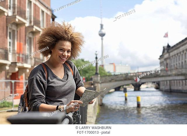 Portrait of smiling female tourist standing with map against Fernsehturm, Berlin, Germany
