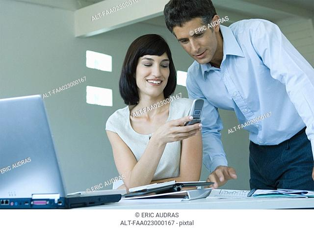 Young businesswoman holding up cell phone to mature male colleague, smiling