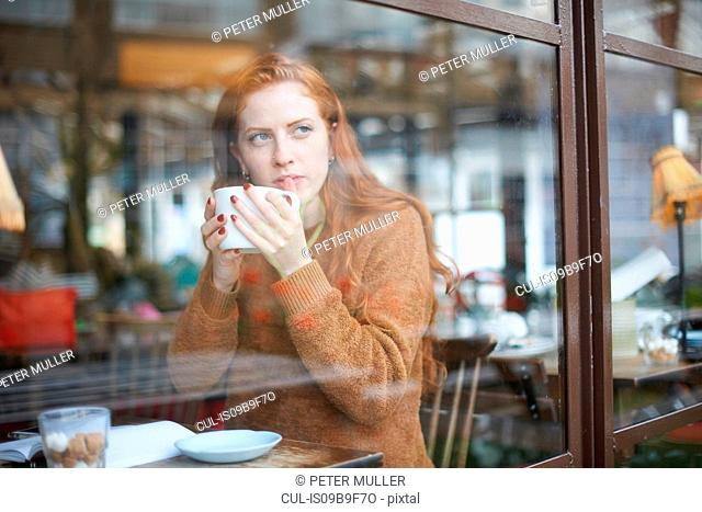 View through window of woman in coffee shop holding cup