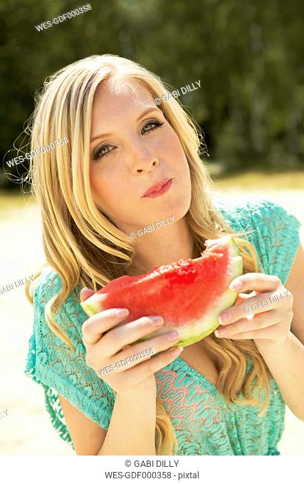 Portrait of young woman eating slice of watermelon