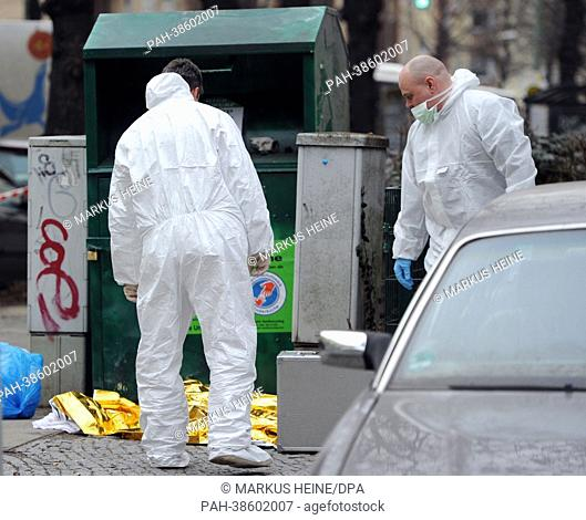 Forensic scientists stand in front of a used-clothes container where a dead baby was found in Berlin Neukoelln, Germany, 05 April 2013