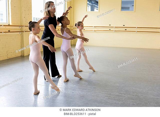 Teacher and students practicing in ballet studio