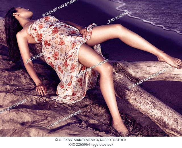 Young sexy woman in wet summer dress lying on a driftwood on a shore at sunset