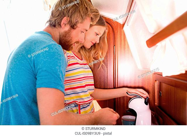 Young couple in sailboat cabin using coffee machine