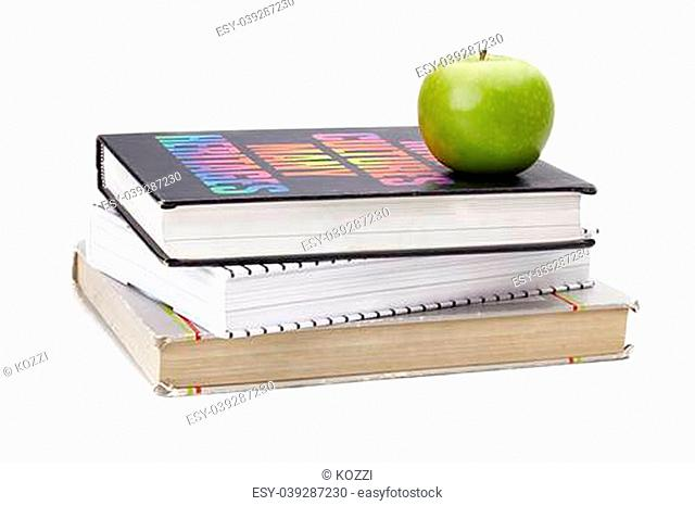 Granny Smith green apple on top of a pile of books