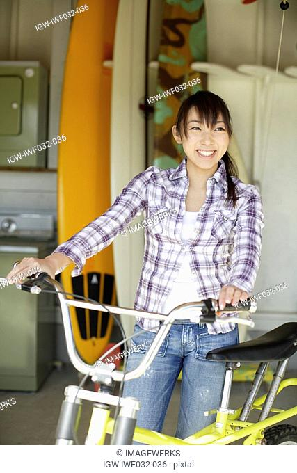 View of a smiling woman with bicycle