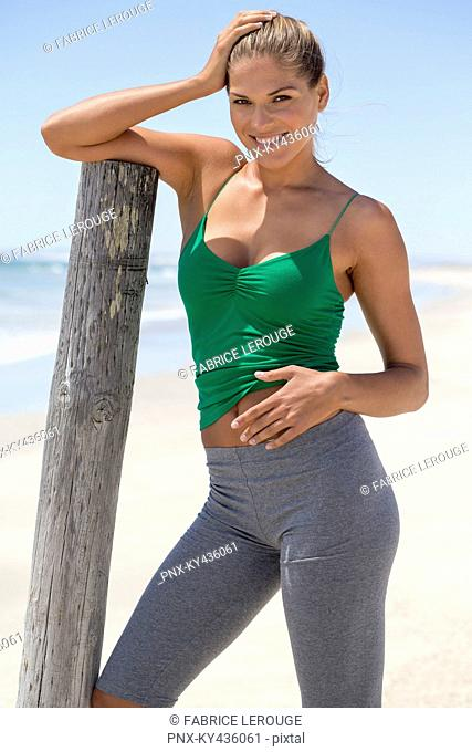 Smiling woman leaning against a wooden post on the beach