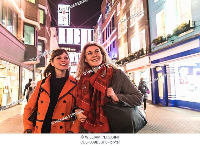 Two female friends walking along street, dusk