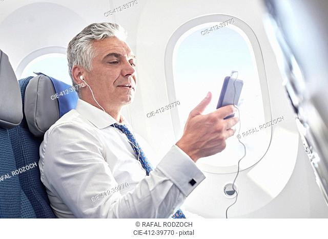 Businessman listening to music with headphones and mp3 player on airplane