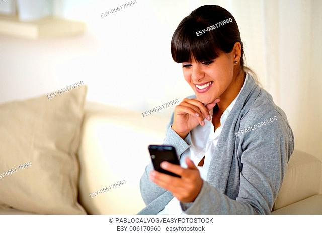 Portrait of a charming young woman reading message on cellphone while is sitting on couch at home