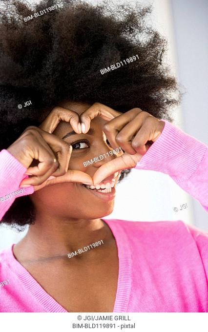 Mixed race woman making heart-shape with fingers