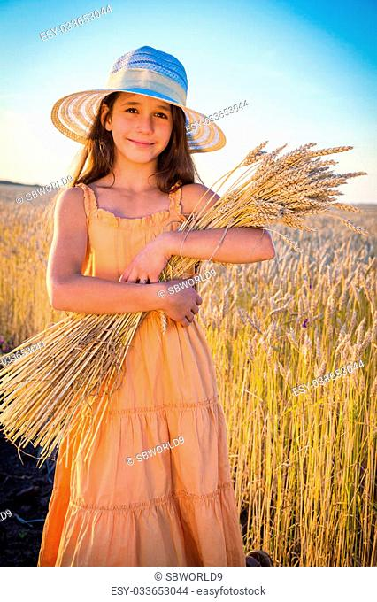 Smiling girl with sheaf of wheat standing on the field