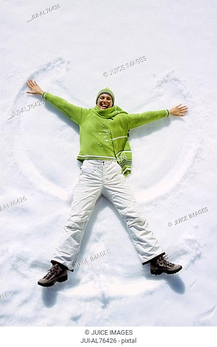 High angle view of a young woman making a snow angel