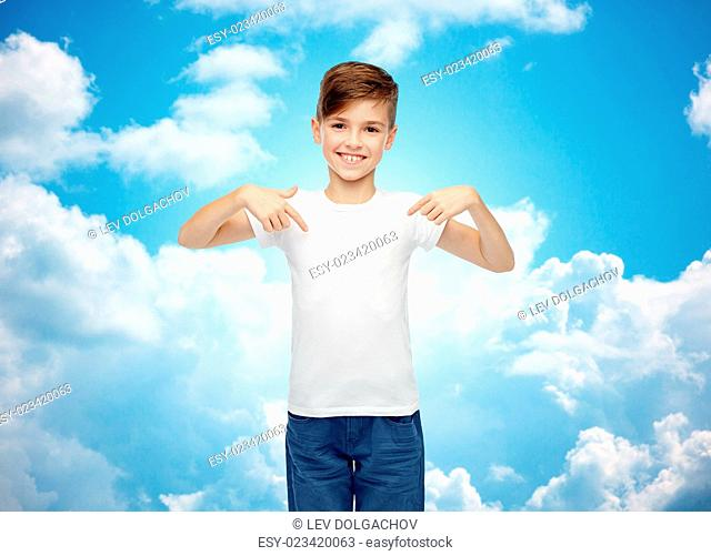 childhood, fashion, advertisement and people concept - happy boy in white t-shirt and jeans pointing finger to himself over blue sky and clouds background