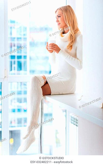 Enjoying fresh coffee at home. Beautiful young woman in warm sweater and socks drinking coffee and looking through a window at home