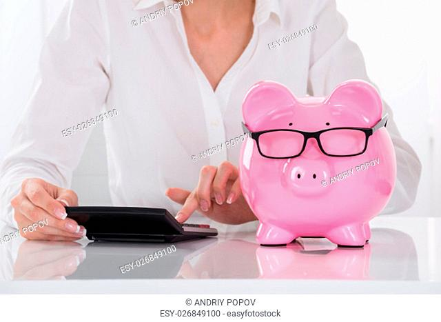Businesswoman Using Calculator With Piggybank On Desk