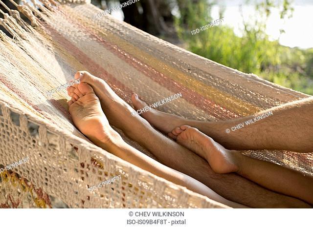 Couple relaxing in hammock, view of legs