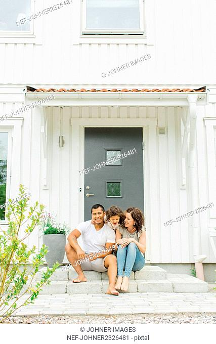 Family sitting in front of house
