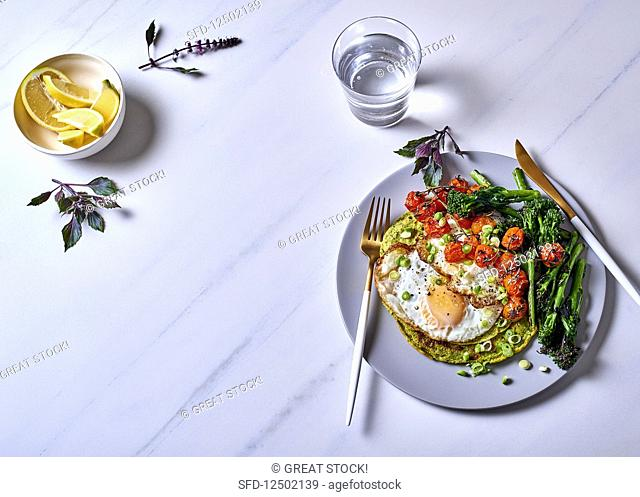 Green chickpea pancakes with fried eggs, charred broccolini and vine tomatoes