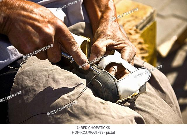 Close-up of a cobbler repairing a shoe, HohHot, Inner Mongolia, China