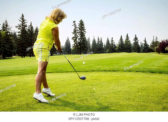 A woman golfer driving a ball down the fairway from the tee off during a golf tournament on a warm summer day; Edmonton, Alberta, Canada