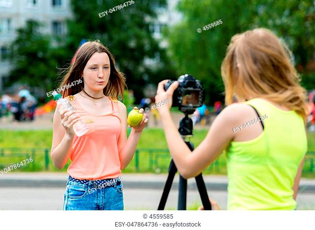2 girls talk about fruits. Healthy brother lives proper diet. In her hands holds bottle water and apple. Record vlog and blog subscribers