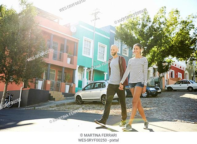 South Africa, Cape Town, young couple walking hand in hand on the street