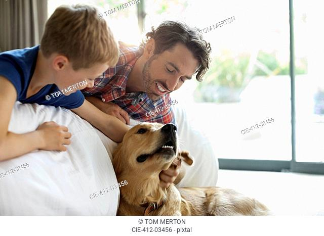 Father and son petting dog on sofa
