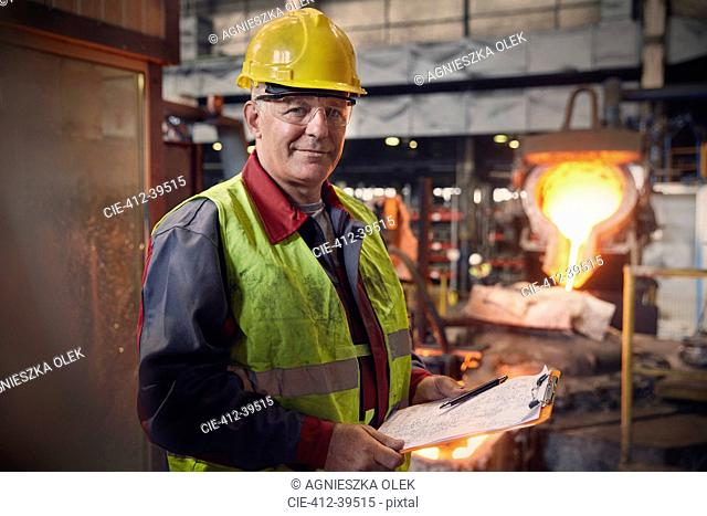 Portrait confident steelworker supervisor with clipboard in steel mill