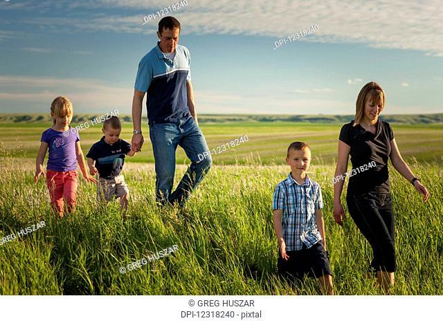 A family walks through a farm field; Herschel, Saskatchewan, Canada