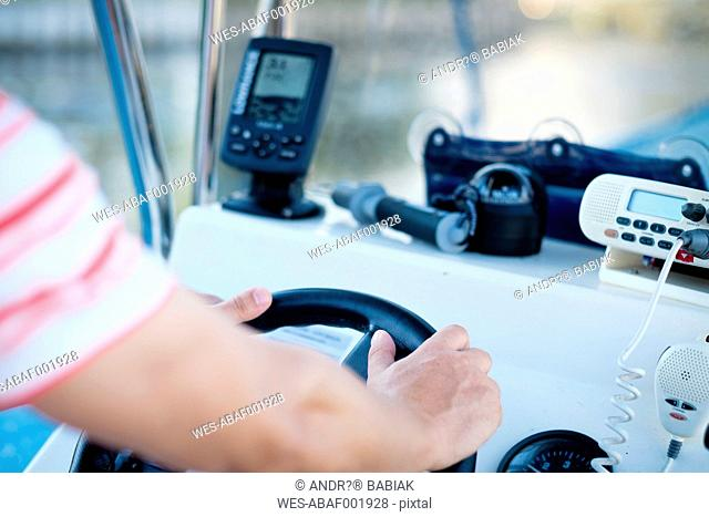 Hands at the steering wheel of a fishing boat with fish finder, GPS , compass and VHF radio
