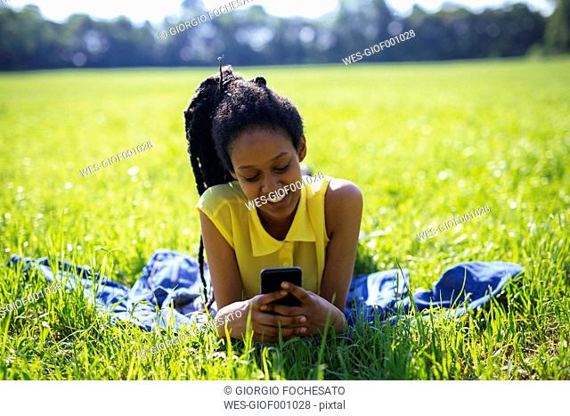 Portrait of young woman with smartphone relaxing on a meadow