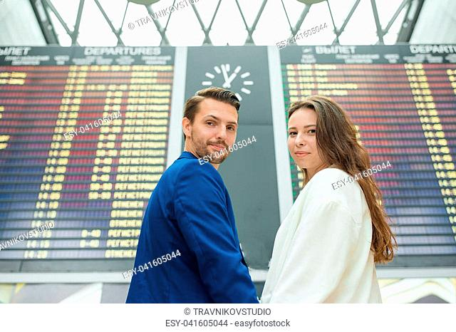 Portrait of young family in front of flight information board at airport