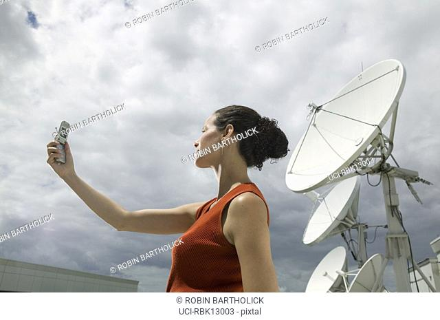 Young businesswoman talking on cell phone with satellites