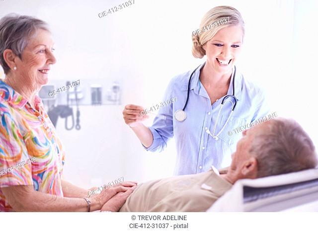 Smiling doctor checking senior man's temperature