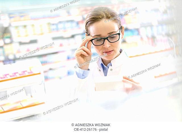 Pharmacist reading label on box in pharmacy