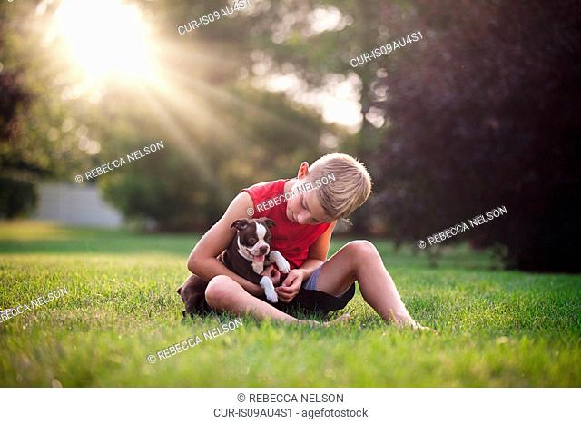 Front view of boy sitting on grass holding Boston Terrier puppy, looking down