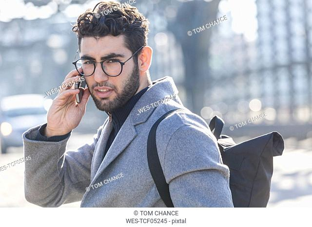 Portrait of young businessman with backpack on the phone