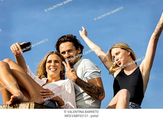 Friends having fun on a rooftop terrace, taking selfies